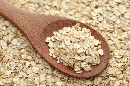 Rolled oats (oat flakes) in a wooden spoon on a rolled oats background. Close-up.